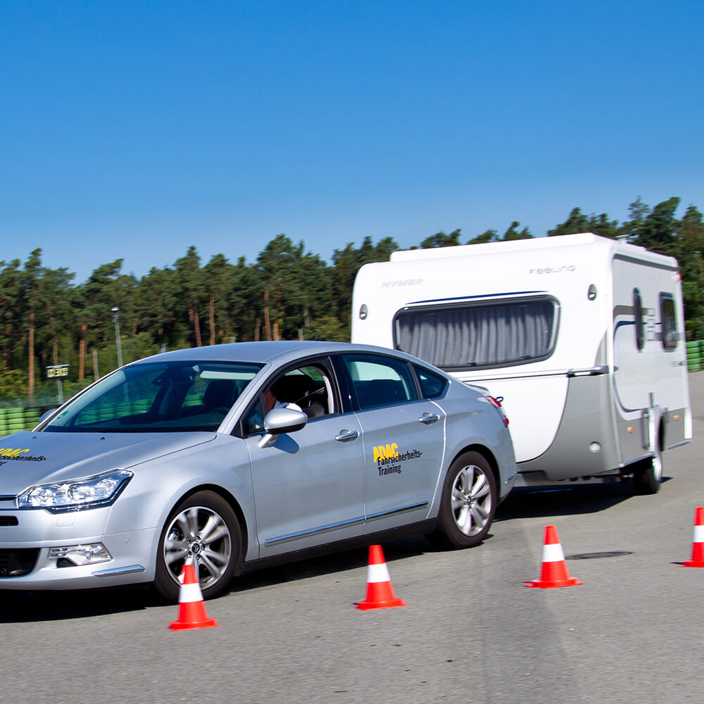 Caravan-/ Gespann-Training: Pkw mit Caravan-Anhänger fährt an aufgestellten Verkehrskegeln vorbei.