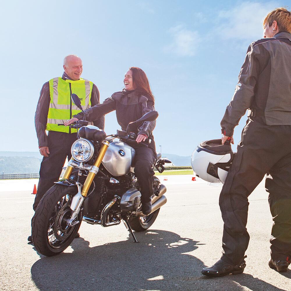 Motorrad-Frauen-Training: Motorradfahrerin sitzt auf Motorrad und der Trainer steht mit Warnweste daneben.