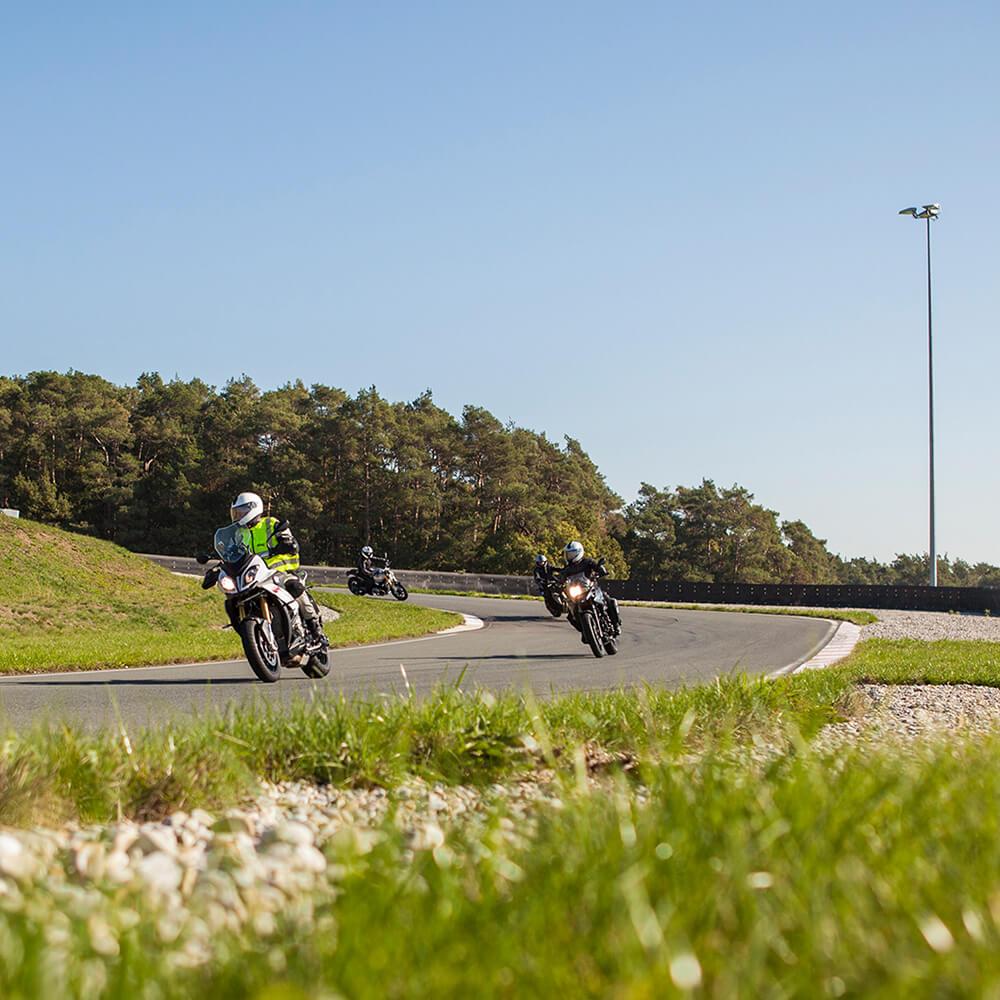 Motorrad Fun and Safe Training: Vier Motorradfahrer fahren hintereinander auf dem Trainingsgelände in eine Kurve.