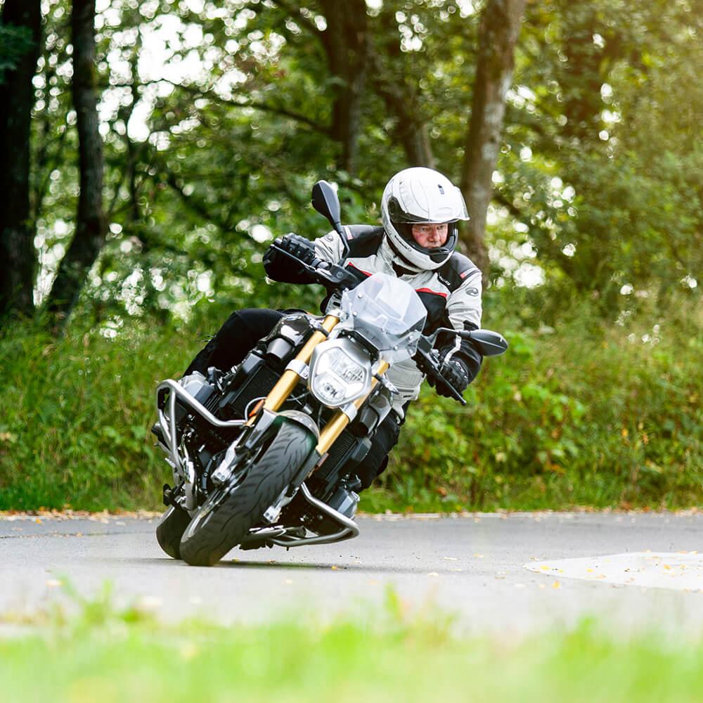 Motorrad-Basis-Plus-Training: Motorradfahrer fährt auf dem Trainingsgelände und lehnt sich in eine Kurve.