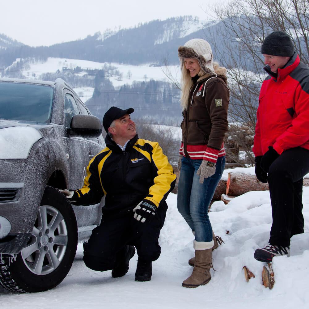 Pkw-Winter-Training: Pkw steht in mit Schnee bedeckter Straße. Trainer und zwei Teilnehmer. Trainer zeigt auf Autoreifen.
