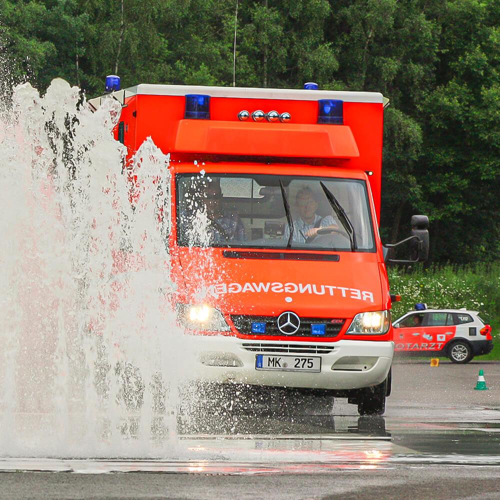 Rettungswagen fährt auf Trainingsgelände durch Wasserfontäne