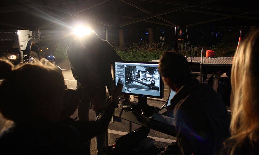 Filmproduktionsset: Aufnahme bei Nacht. Mitarbiter schauen hinter den Kulissen auf einen Bildschirm.